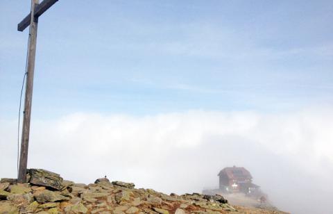 Das Schutzhaus Zirbitzkogel taucht aus dem Nebel auf – Etappe 17 Panoramaweg Südalpen